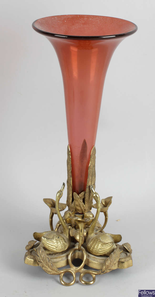 A Victorian gilt metal and cranberry trumpet shaped vase.