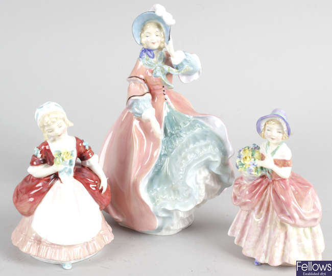 A Royal Doulton bone china figurine, together with two similar smaller examples.