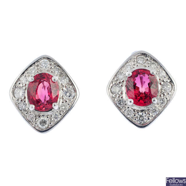 A pair of red sapphire and diamond earrings.