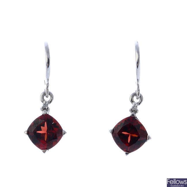 A pair of garnet and diamond earrings.