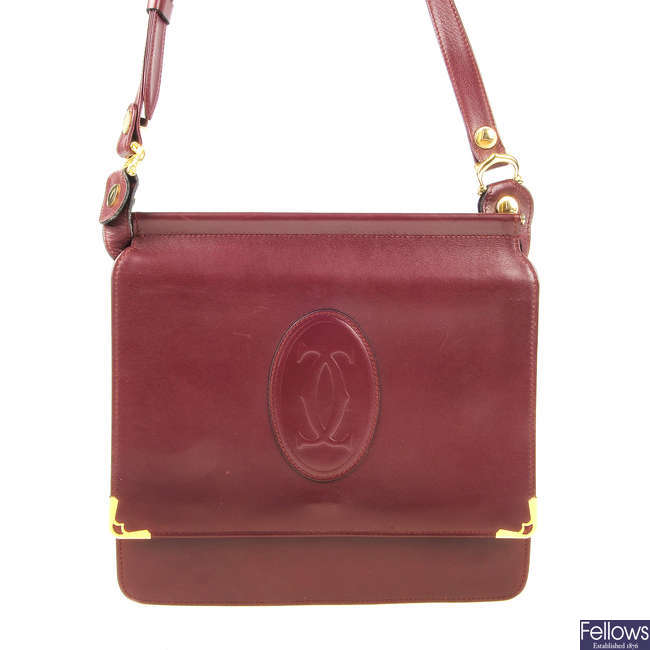 CARTIER - a reversible Must De Cartier Bordeaux messenger handbag.