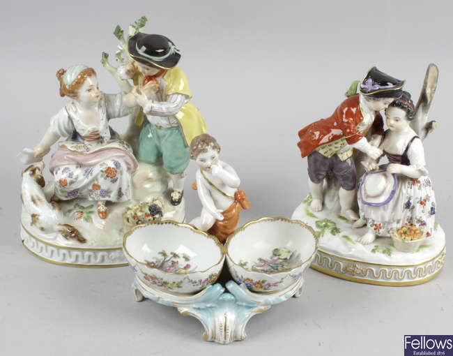 A pair of German porcelain figure groups, together with a Berlin porcelain figural mounted twin compartment dish.
