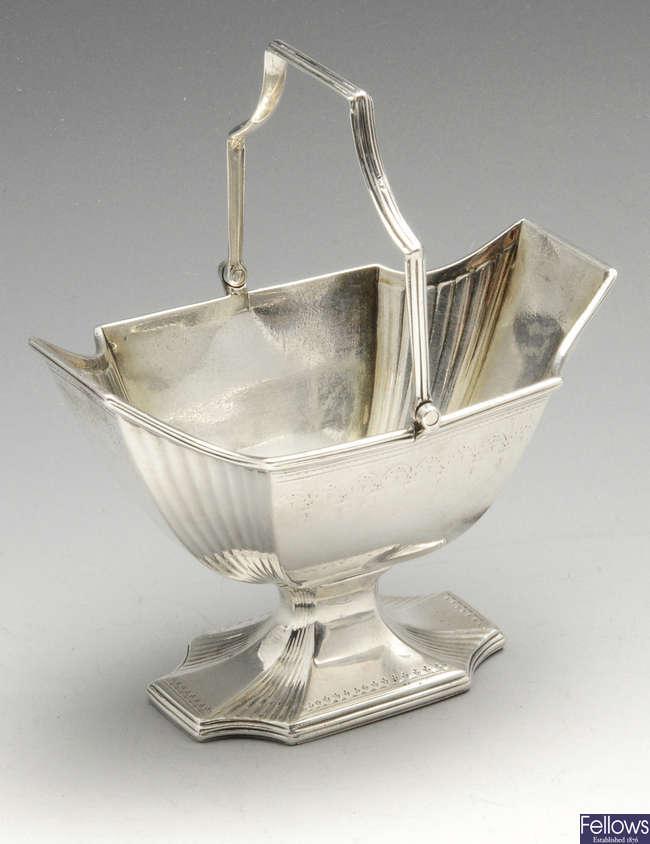 A George III silver swing-handled sugar basket of pedestal form.