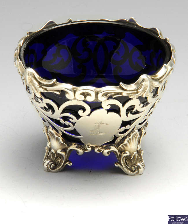 A Victorian silver pierced open salt or dish with blue glass liner.