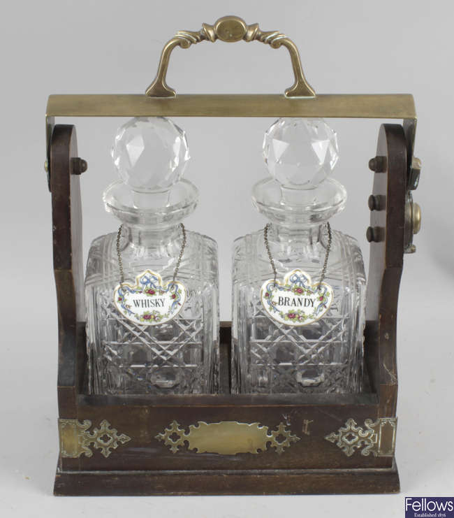 A stained wooden two bottle tantalus frame, with brass mounts, the twin cut glass decanters with globular prismatic cut stoppers.