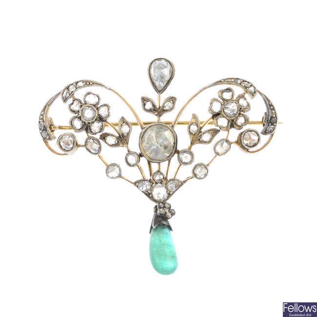 A diamond and emerald brooch.