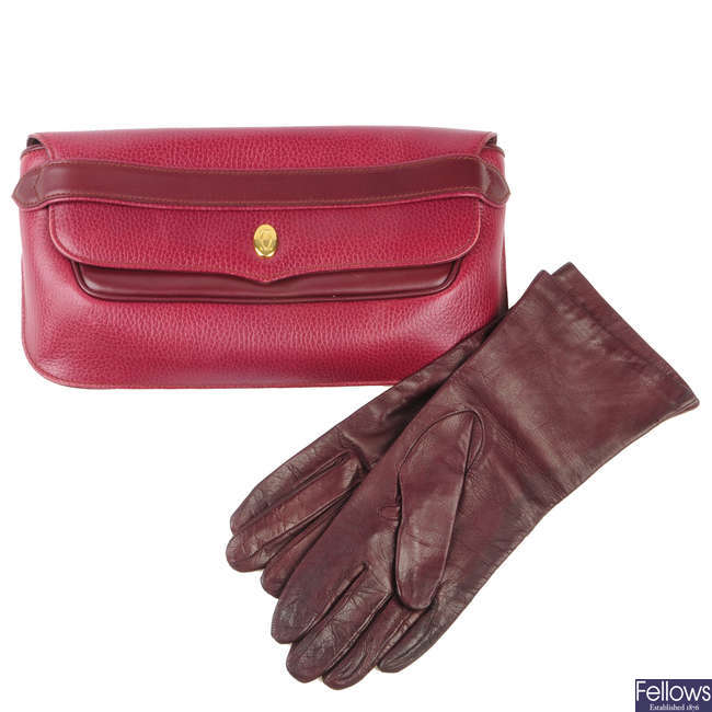 CARTIER - a Bordeaux leather clutch and a pair of leather gloves.