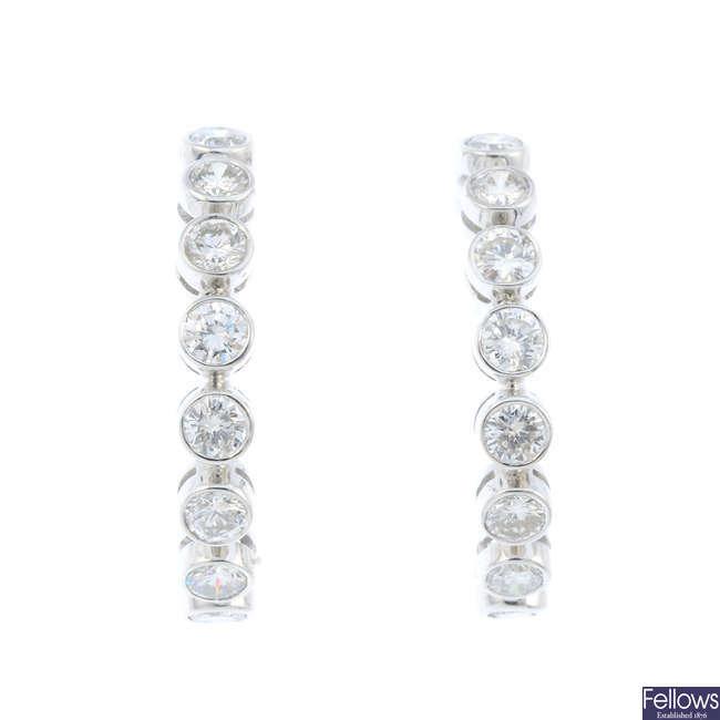 A pair of 18ct gold diamond hoop earrings.
