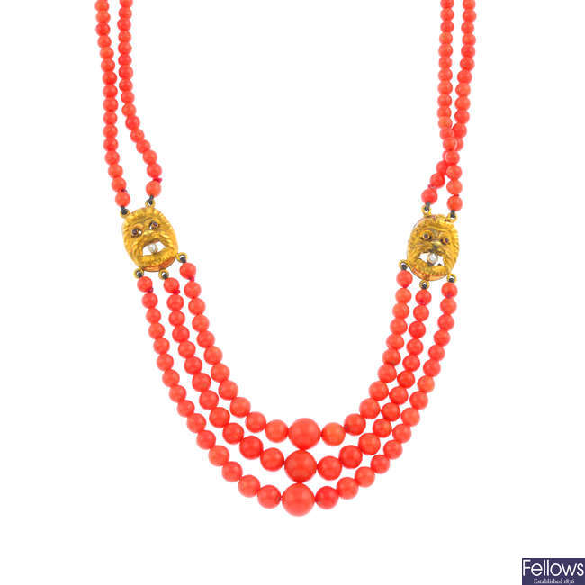 A coral, ruby and diamond Greek theatre mask necklace.