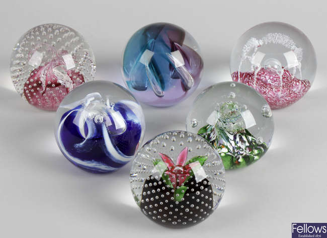 A collection of assorted coloured glass paperweights, to include a selection of Caithness and other named examples.