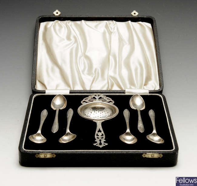 A matched 1930's cased set of six silver teaspoons and a tea strainer.
