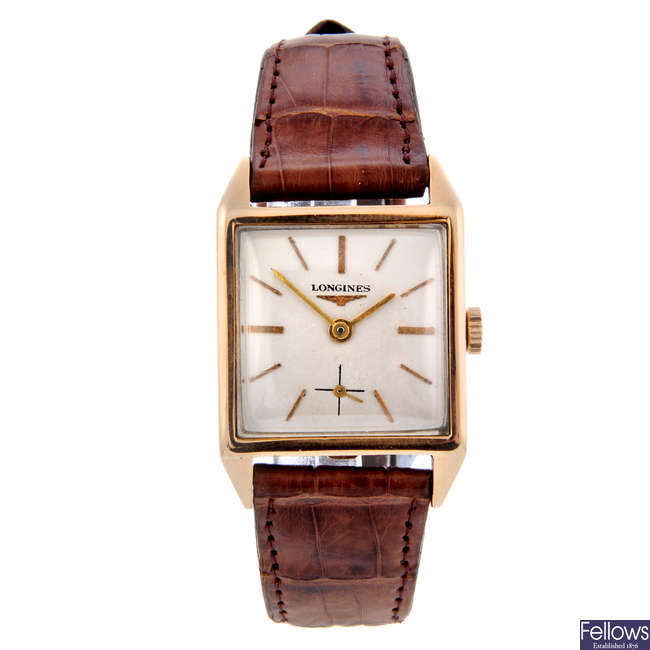 LONGINES - a mid-size yellow metal wrist watch.