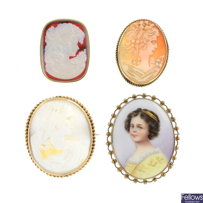 Three cameo brooches and a porcelain brooch.