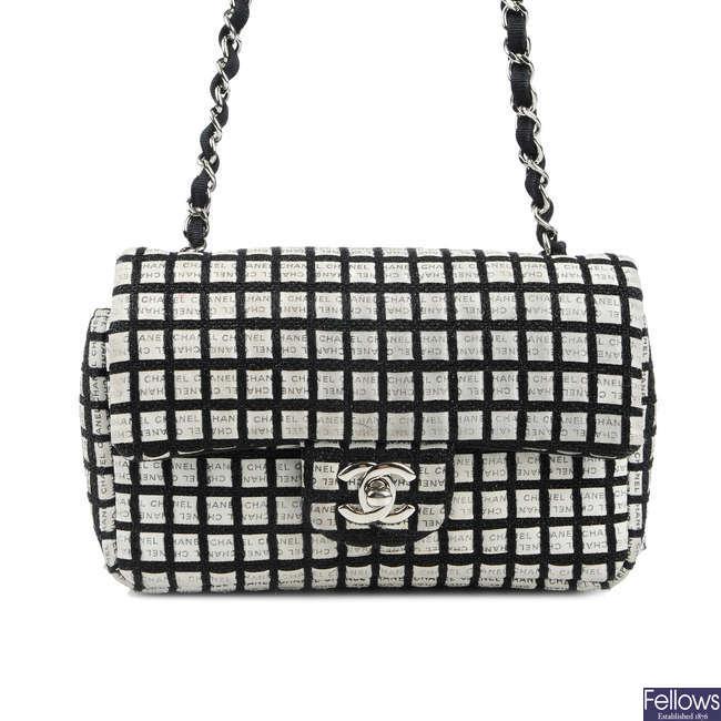 CHANEL - a black and white woven New Mini Flap handbag.