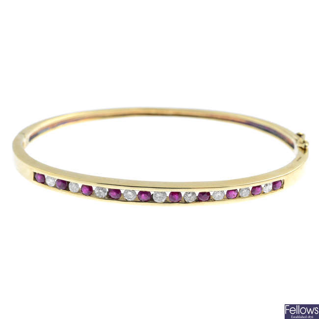 A 9ct gold diamond and ruby hinged bangle.