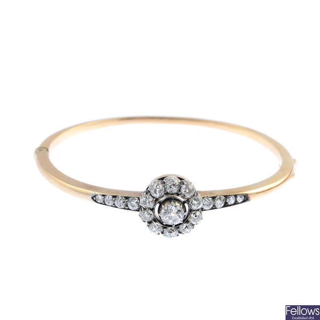 An early 20th century gold diamond cluster hinged bangle.
