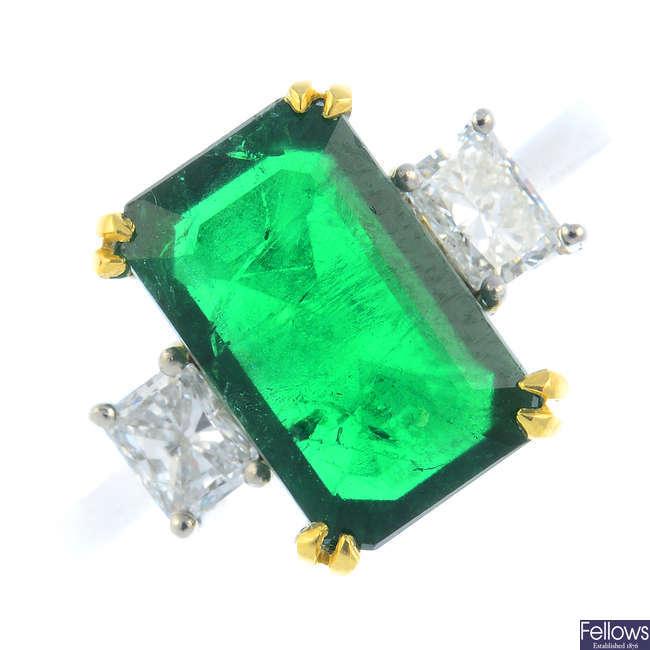 A platinum emerald and diamond three-stone ring.
