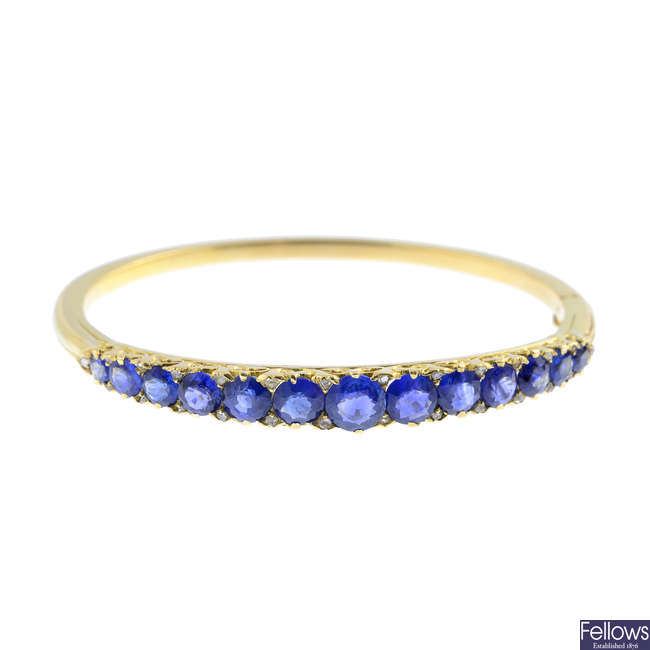 An early 20th century 18ct gold, sapphire and diamond hinged bangle.