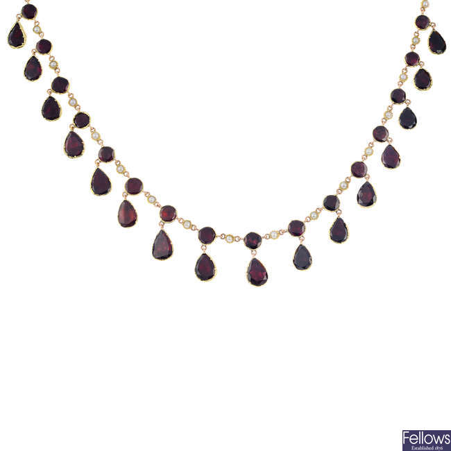 A gold foil-back garnet and split pearl necklace.