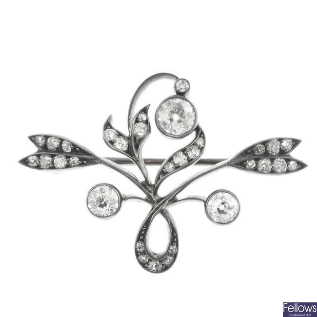 An Art Nouveau silver and gold diamond floral brooch.