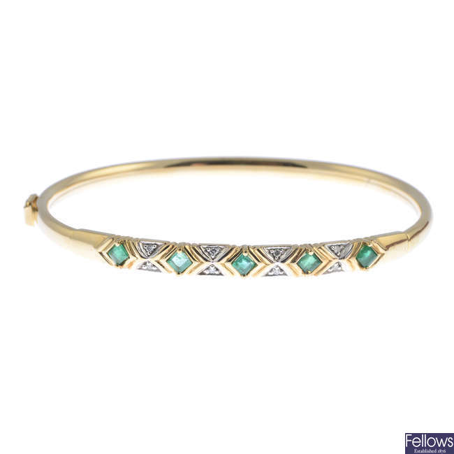 An emerald and diamond bangle.