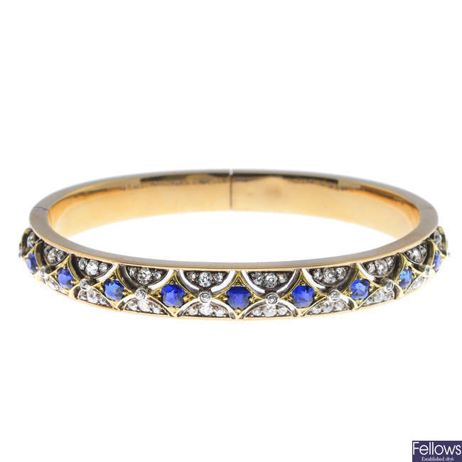 A late Victorian gold sapphire and diamond hinged bangle.
