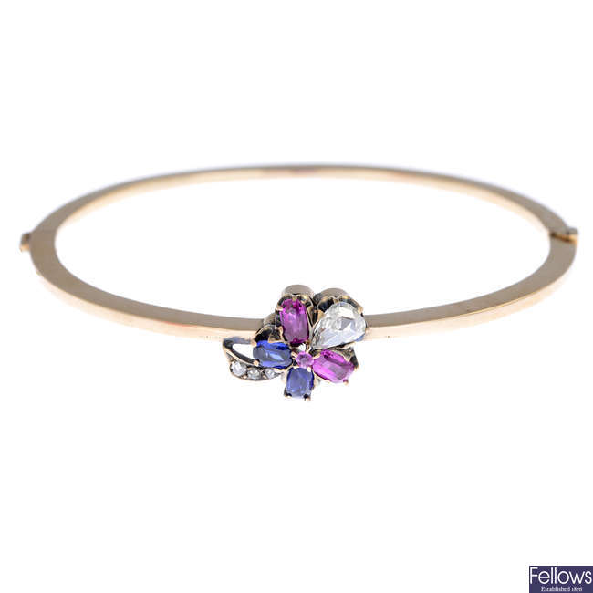 An early 20th century gold diamond, ruby and sapphire hinged bangle, with pansy motif.