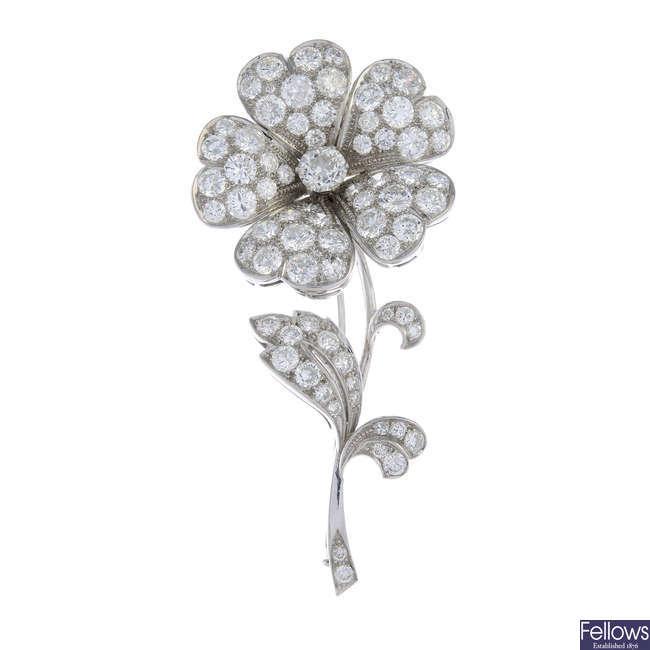 A gold diamond flower brooch.
