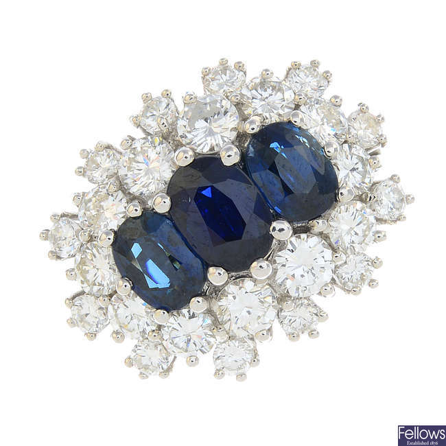 A sapphire three-stone and diamond cluster ring.