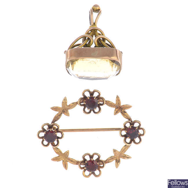 An early 20th century gold garnet brooch and an early 20th century gold citrine fob.
