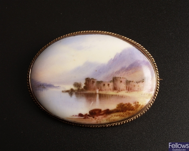 An oval porcelain painted brooch depicting a