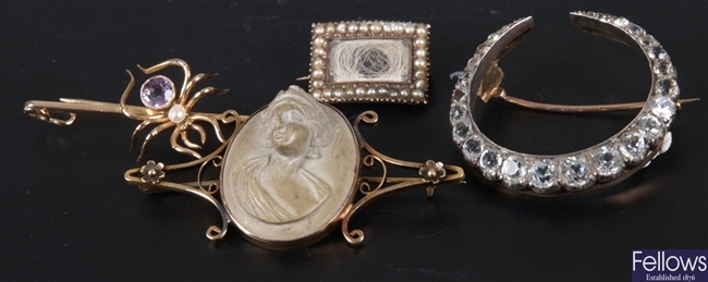 Four brooches to include a gold mounted oval lava