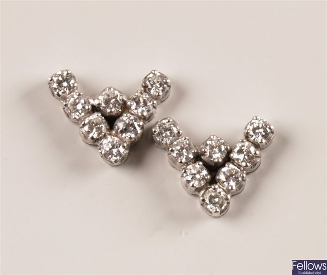 A pair of 'V' shape stud earrings each set with