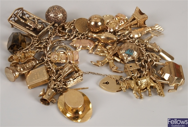 9ct gold charm bracelet with approximately 40