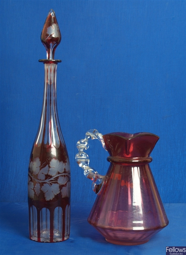 A Victorian cranberry glass jug with clear glass