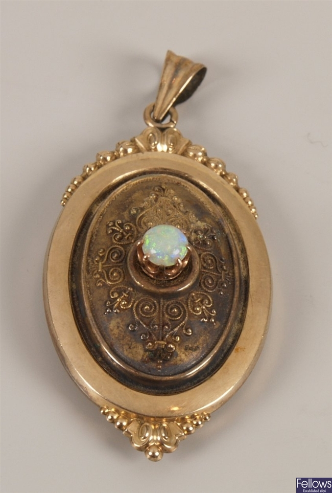 Oval opal set locket with a central round opal