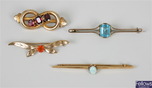 Four brooches to include a three stone red garnet