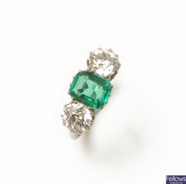 An emerald and diamond three stone ring, centred