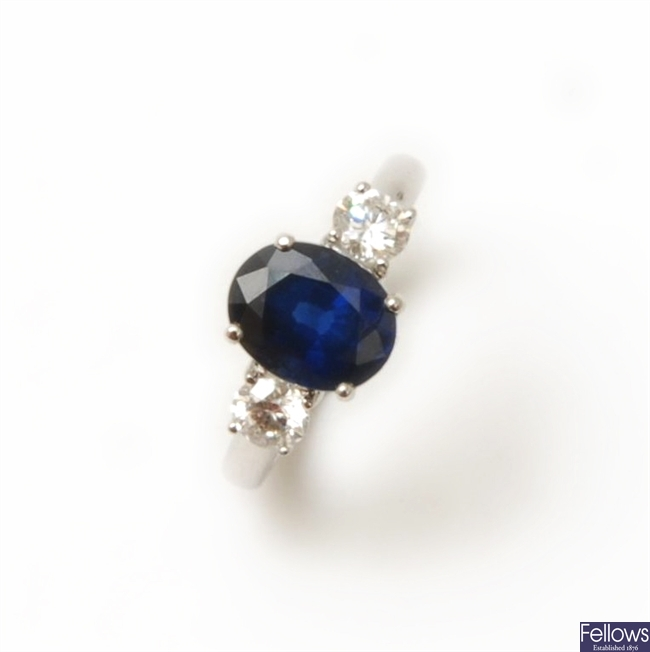 A three stone sapphire and diamond ring, with a