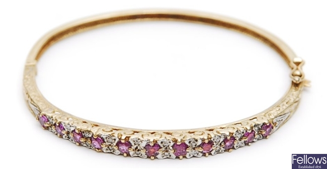 A 9ct gold ruby and diamond set hinged bangle,