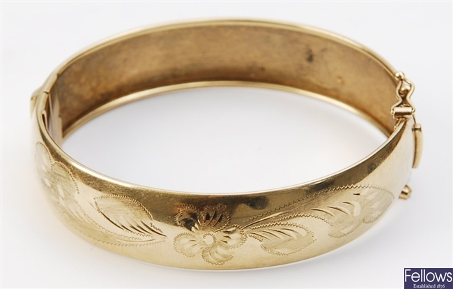 A 9ct gold hinged bangle, with engraved floral