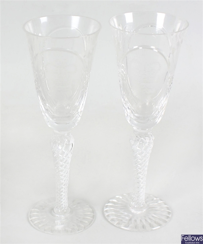 A pair of commemorative wine glasses and a selection of other glasses