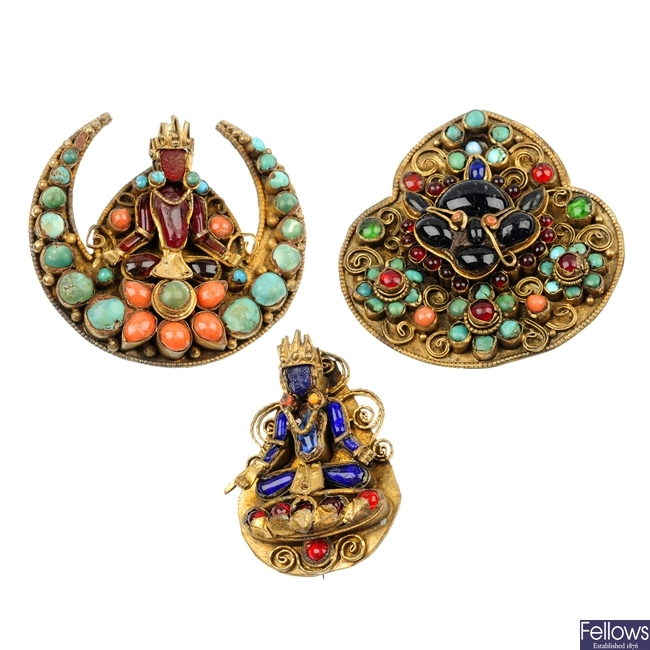 Three multi-gem brooches and a pendant.