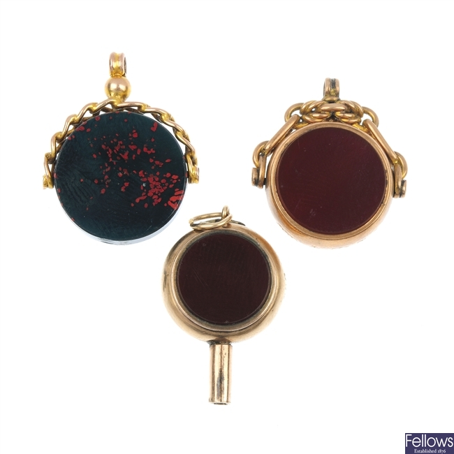 Two early 20th century gold swivel fobs, a gold watch key and a Masonic sphere pendant.