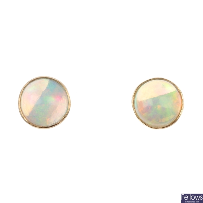A pair of circular opal cabochon ear studs.