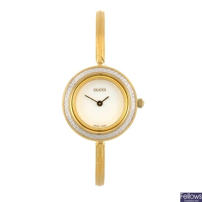 A gold plated quartz lady's Gucci bangle watch.