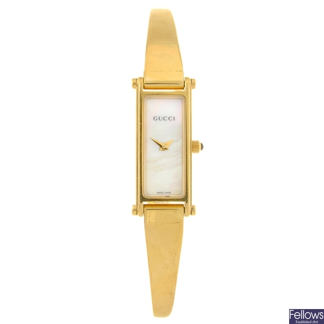 A gold plated quartz lady's Gucci bangle watch.