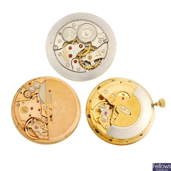 A group of three watch movements.