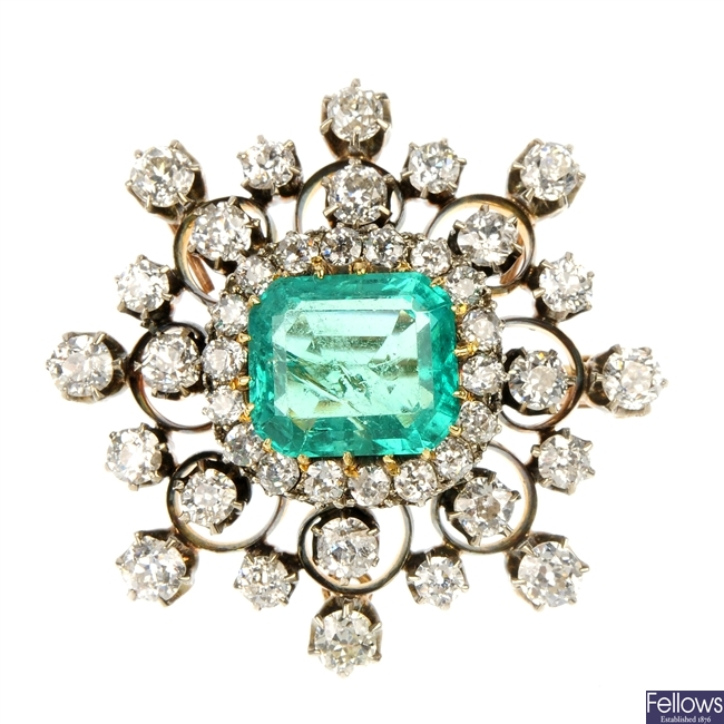 A late Victorian silver and gold emerald and diamond cluster brooch.