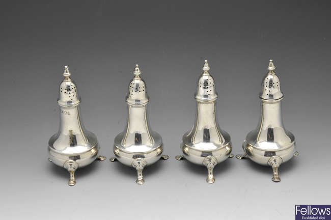 A set of four George III silver pepper casters.